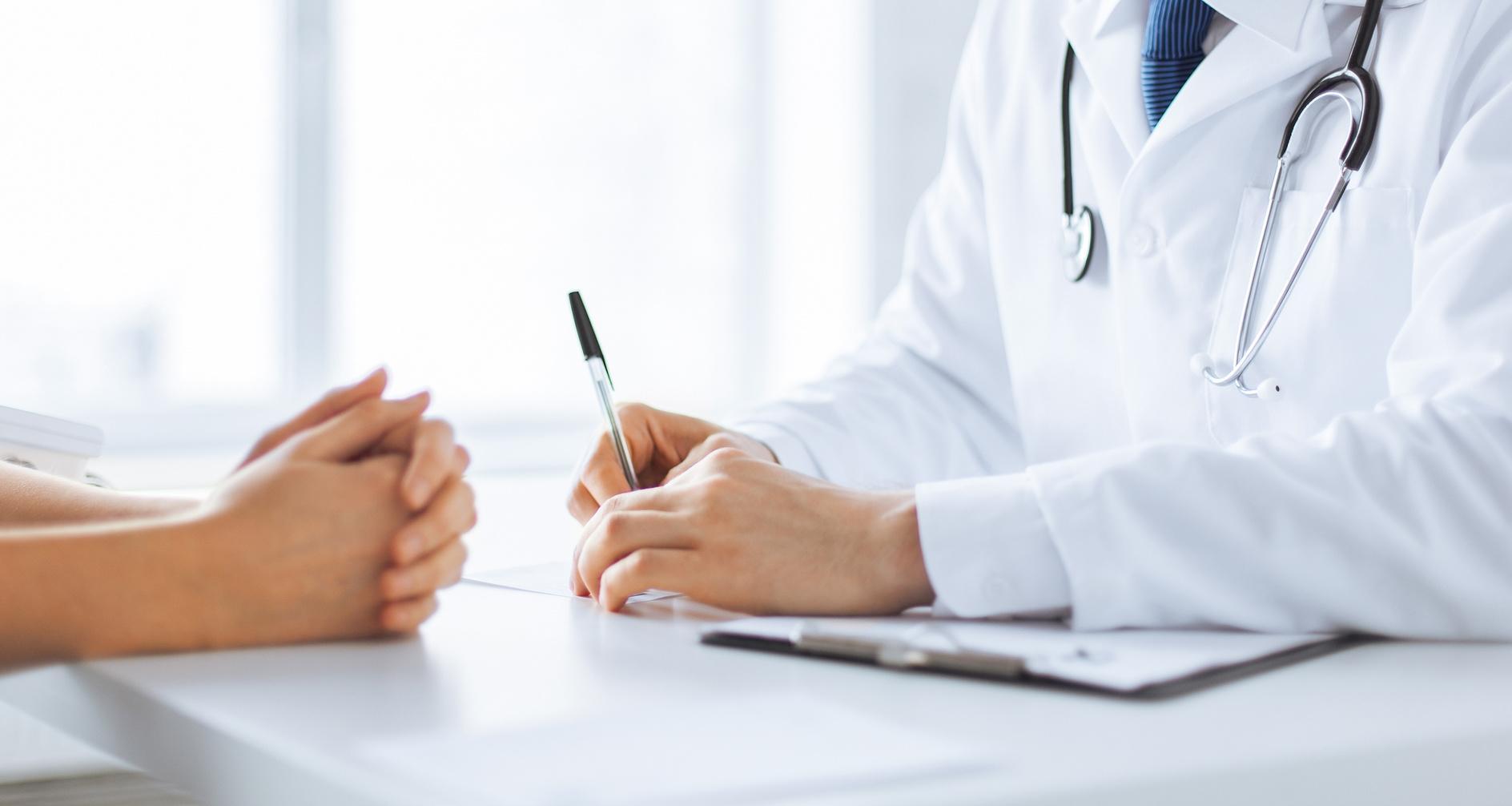 Arzt macht sich Notizen währen eines Patientengesprächs
