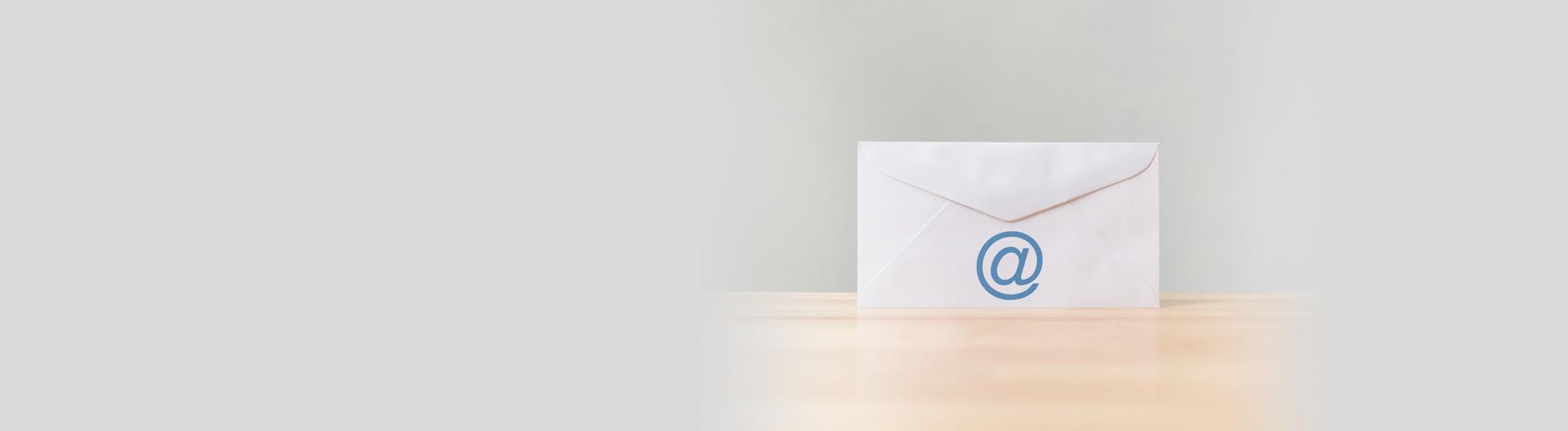 Briefumschlag mit Symbol e-Mail-Adresse auf einem Holztisch