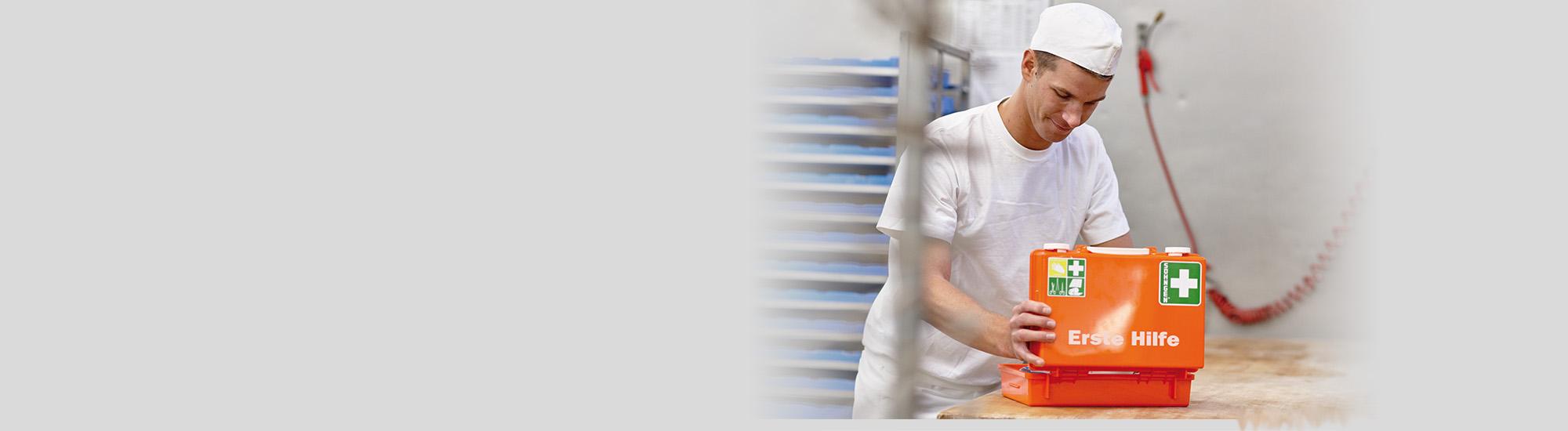 Ein junger Bäcker öffnet einen Erste-Hilfe-Kasten