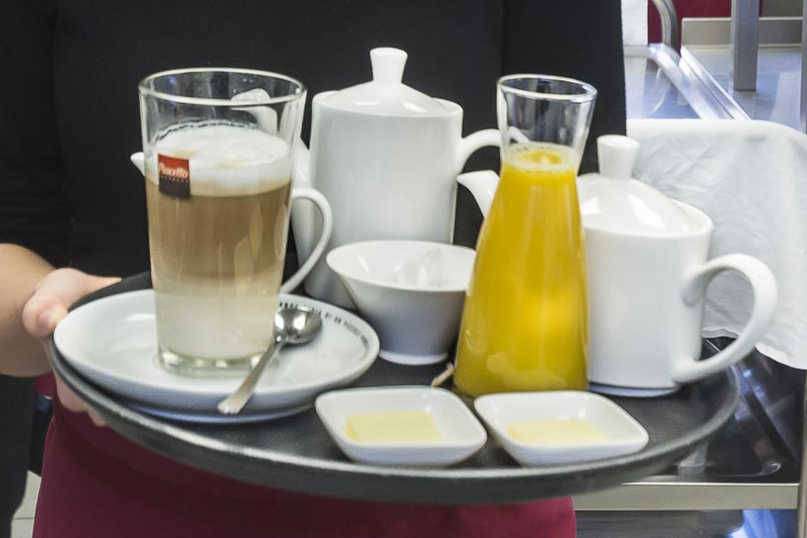 Servicekraft mit Getränken auf einem Serviertablett