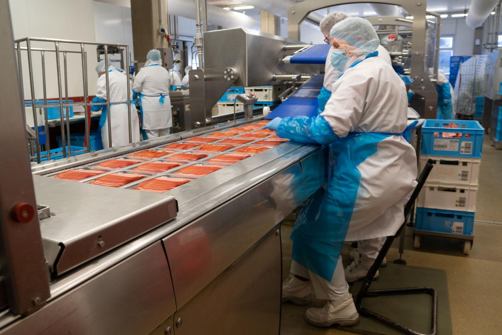 Eine Mitarbeiterin sitzt an einer Verpackungsmaschine, auf der Wurstwaren übers Band laufen.
