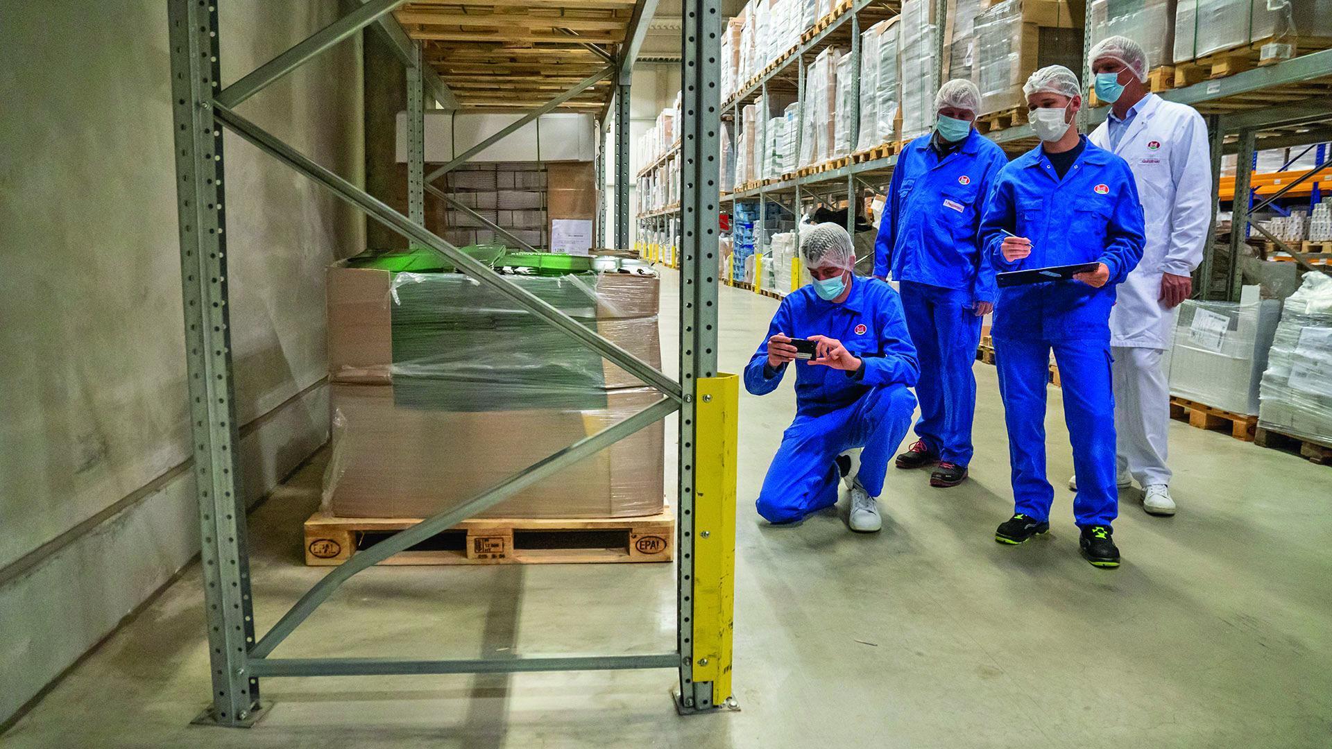 Vier Mitarbeiter in Schutzkleidung auf einem Rundgang in einer Lagerhalle, ein Mitarbeiter kniet und macht ein Foto.