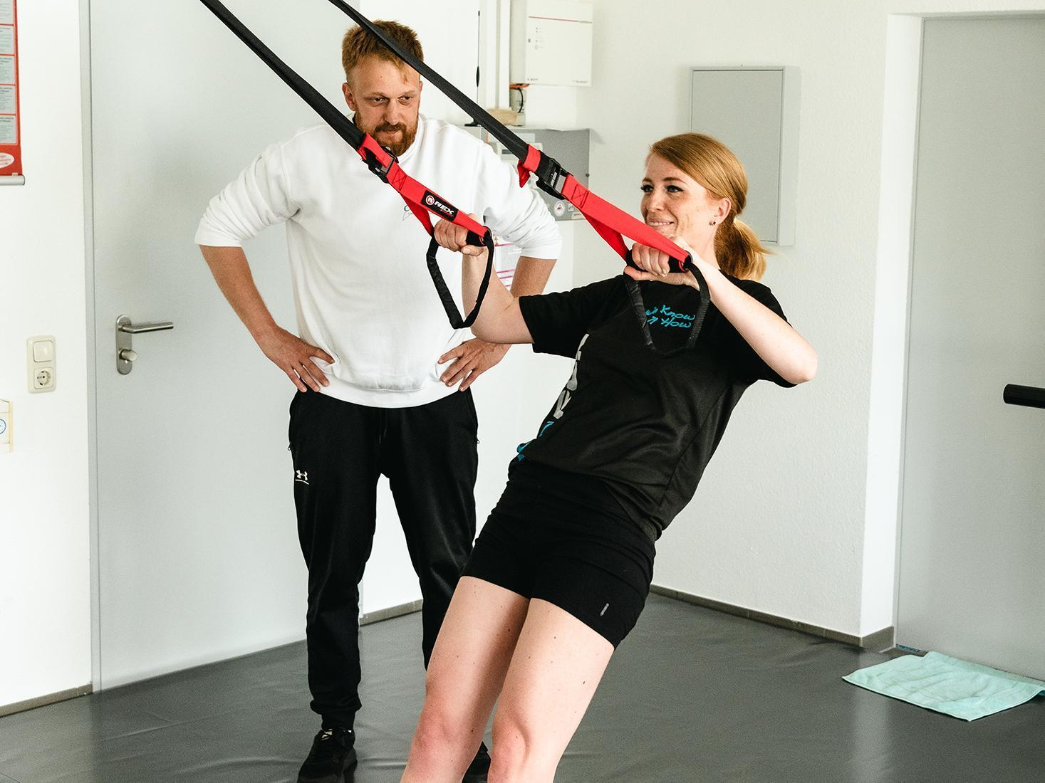 Eine Frau trainiert mit Zugbändern, ein Mann steht daneben und überwacht.